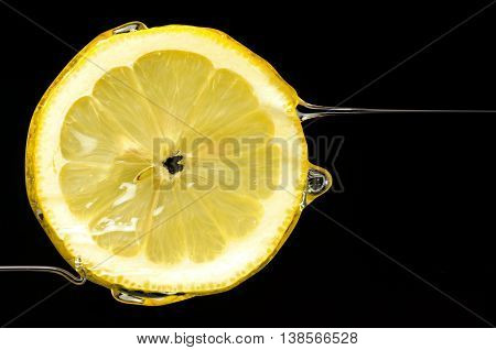 Slice of lemon with horizontal drops of juice