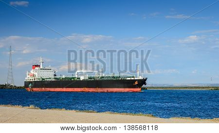 Oil products tanker heading to the port through canal