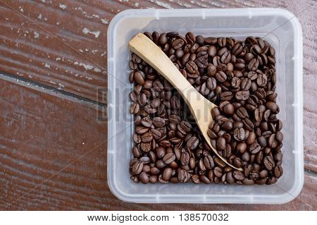 Coffee beans square shaped box with wooden spoon. Wooden surface.