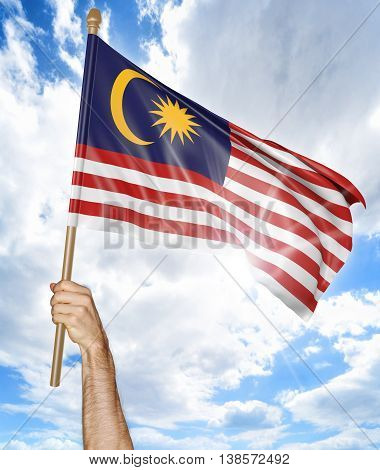 Person's hand holding the Malaysian national flag and waving it in the sky, 3D rendering