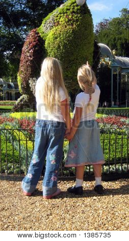 Girls Standing Hand In Hand Looking At A Design