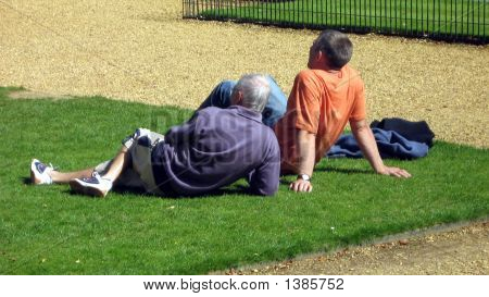Two Men Sitting Relaxing On Grass.