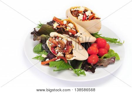 Pitta bread on salad leaves filled with a chicken vegetables and feta cheese