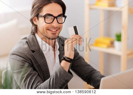 Pay it off. Cheerful handsome bearded man sitting at the table and holding credit card while using laptop