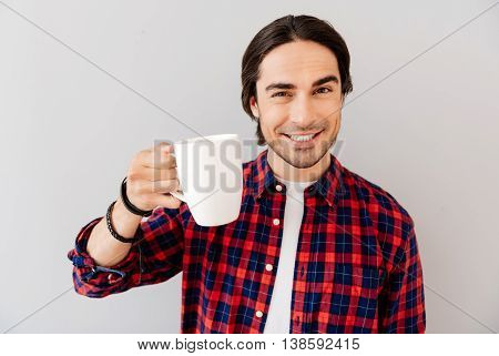 Energy booster. Positive handsome emotional man holding cup and drinking coffee while standing isolated on grey background poster
