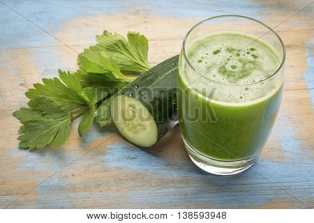 fresh green vegetable juice  with cucumber and celery leaf against grunge wood