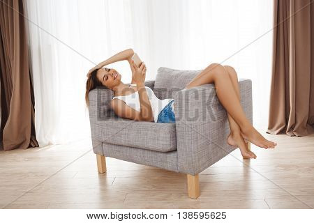 Attractive young girl laying in armchair and chatting at living room