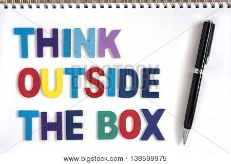 Colorful wood letters word think outside the box in open notebook with a pen Quotes business concept