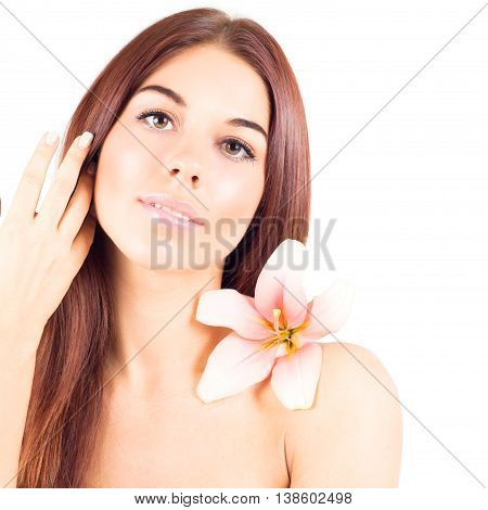 Beautiful woman with clean skin and with flower touching hair. Facial result.