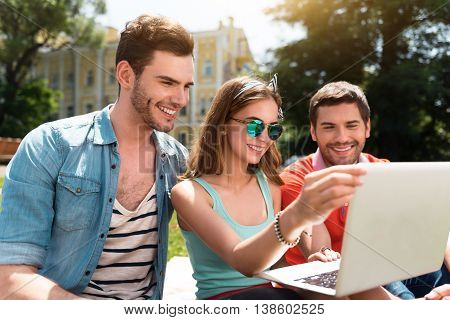 Stay up to date. Positive and delighted young woman and two young men using laptop during their studying while being in the park and sitting on the grass