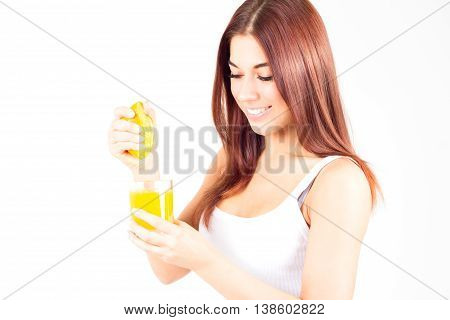 Healthy happy woman squeezes juice from orange and looking down. Healthy and right food.
