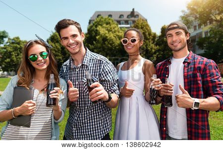 Millennials. Happy and glad group of young people holding cola while standing in the park together and gesturing