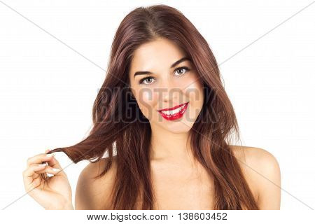 Sexy smiling tanned woman with red lips. Woman with make up. Tanned woman playing with her hair.