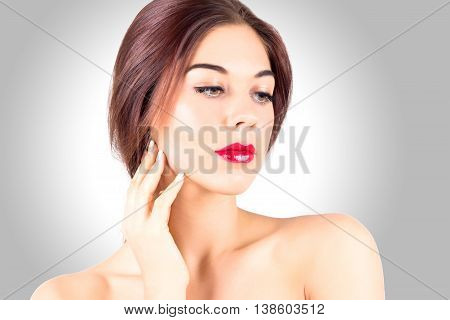 Sexy young woman with beautiful red lips looking down on gray background. Beauty woman with red lips touching cheek.