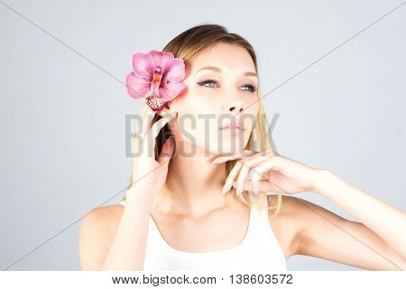 Woman with a pink orchid touching chin with proud look. Beauty blond woman.