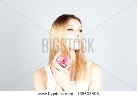 Blond woman with pink flower and permanent makeup. Beauty woman.