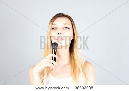Blonde woman holding professional brush for blush. Make up artist.