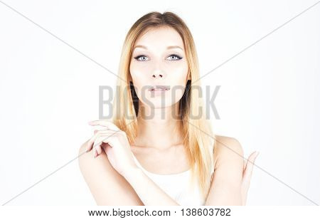 Young woman hugging herself. Permanent makeup. Arrows on the eyes.