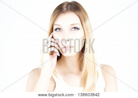 Beautiful woman with a permanent make-up touch her face. Beauty blonde.
