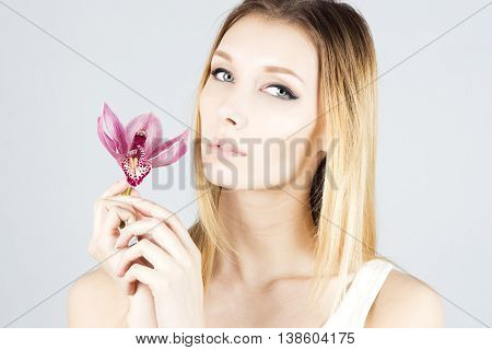 Beauty blonde with with pink flower in hand. Clear and fresh skin. Beauty face.