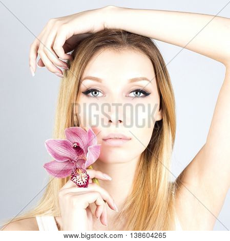 Attractive beautiful blonde with a pink flower. Woman with permanent makeup. Close up portrait of woman.
