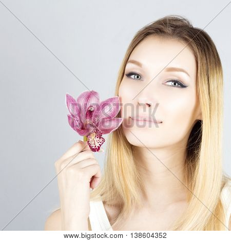 Portrait of smiling blonde with pink flower. Beauty face of woman.