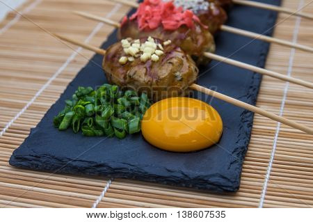 Tsukune - Japanese chicken yakitori meatballs served with chili sauce, chili flakes, ground pepper and lemon wedges.