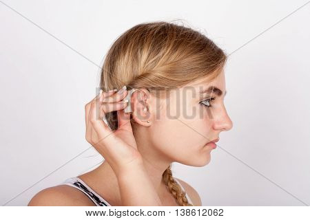 Portrait of a beautiful girl inserting a hearing aid in her ear