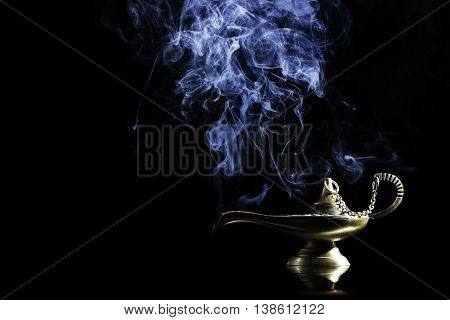 Magic lamp on black background from the story of Aladdin with Genie appearing in blue smoke concept for wishing, luck and magic