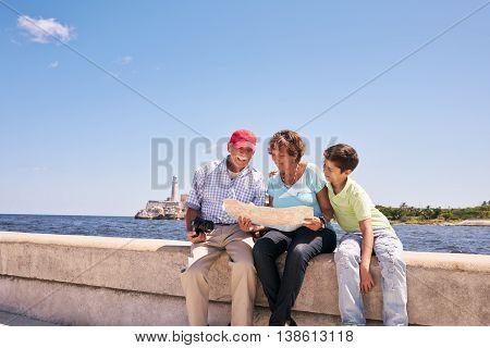 Family Grandparents Reading Tourist Map In Habana Cuba