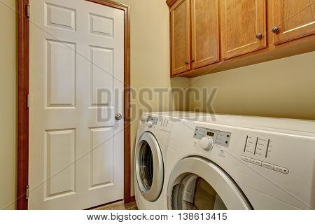 Laundry Room With White Appliances And Light Tone Cabinets