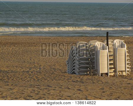 many beach chairs stacked at the end of a day of summer beach
