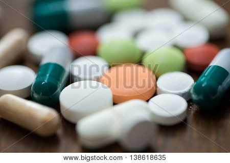 addiction, medication, medicine and substance abuse concept - close up of different drugs in pills and capsules on table