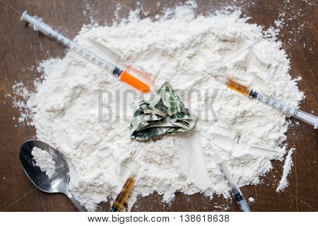 drug use, crime, addiction and substance abuse concept - close up of crack cocaine with money, spoon and syringe