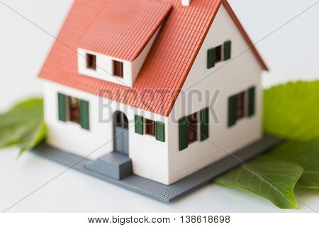 housing, environment and ecology concept - close up of living house model and green leaves