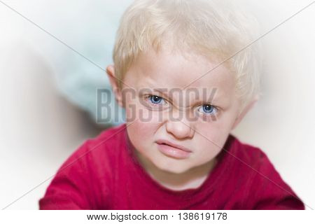 Portrait of dissatisfied little blond with blue eyes and red shirts