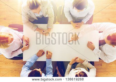 business, people and team work concept - close up of creative team sitting at table and pointing finger to something in office