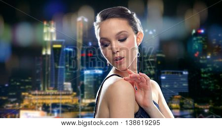 beauty, jewelry, people and luxury concept - beautiful young asian woman with earring over singapore city night lights background