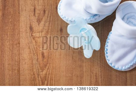 clothing, babyhood, motherhood and object concept - close up of white baby bootees and soother for newborn boy on wooden background