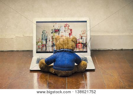 teddy bear watching a film on a laptop computer