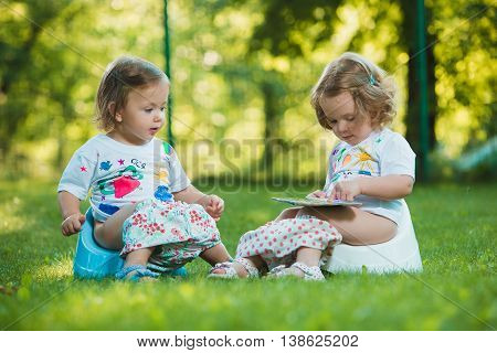 The two little baby girls two-year old sitting on pottys on green grass of lawn