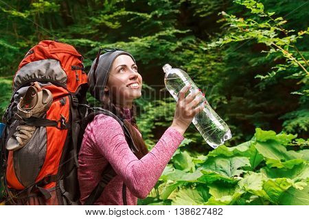 Hiker girl drinking water. Happy woman tourist with backpack drinking water in nature. Young tourist woman drinking water outdoor forest in the background. Beautiful young woman hiking happy with water bottle