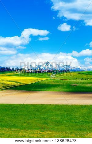 Beautiful Landscape, Green And Yellow Meadow With Field And Snow Mountain And Village. Slovakia, Cen