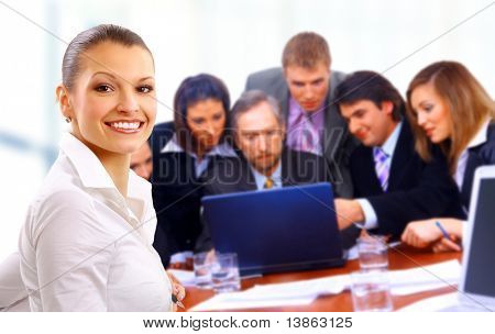 Smiley businesswoman with a group behind him