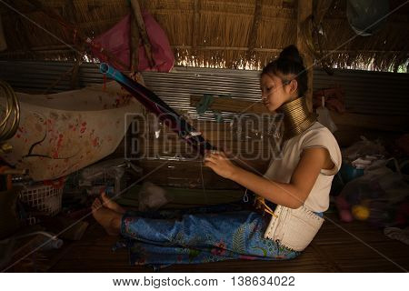 CHIANG MAI, TAILAND - APRIL 22, 2016: A portrait of a woman working at loom in Kayan Lahwi tribe known for wearing neck rings, brass coils to extend the neck. Kayan, Red Karen (Karenni).