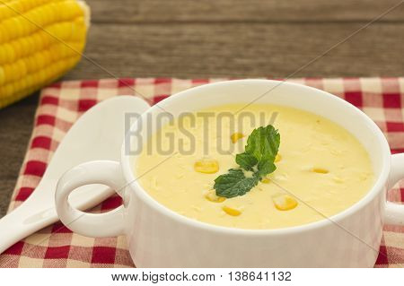 Closeup Cream corn soup on a wooden table.