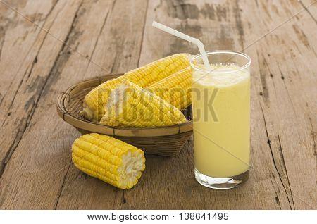 Closeup fresh sweet corn juice (corn milk) on a wooden table.