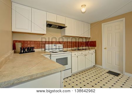 White Kitchen Room With Tile Floor And Brown Back Splash Tile.
