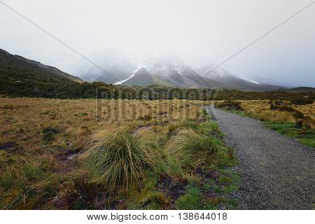 Gravel road leading to snow capped mountain which covered by thick fog.