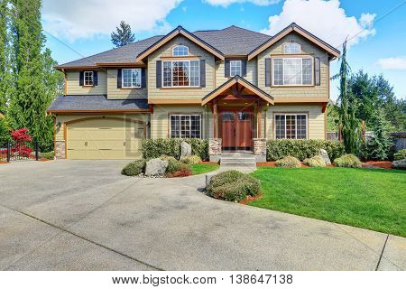 Luxurious Home With Well Kept Lawn And Green Exterior Paint.